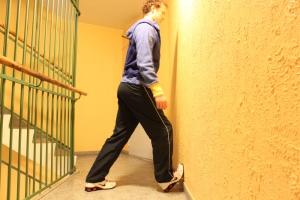 Alternativ 2. Hold kneet i en bøyd posisjon og hoften i vanlig posisjon. Det eneste du beveger er å føre brystet inn mot veggen til du kjenner det tøyer i leggmuskulaturen (den indre muskulaturen).